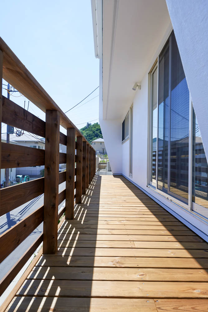 擁壁の上のウッドデッキとシンプルな外構